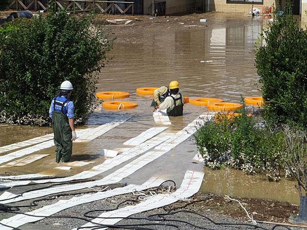 排水準備中の作業員の腰上の高さまで浸水している